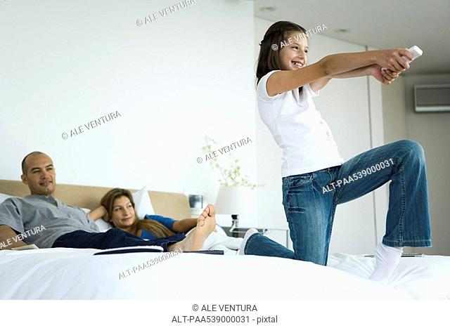 Girl on bed playing video game with wireless controller, parents watching in background