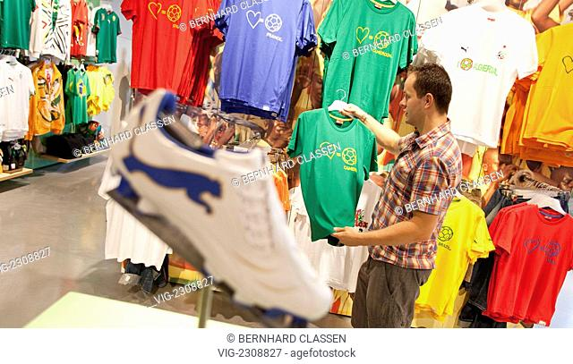 GERMANY, HERZOGENAURACH, 25.06.2010, Factory outlet store of the PUMA AG: client looking for shirts, HERZOGENAURACH, BAVARIA, GERMANY