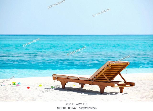 Beautiful scene of one empty beach chair by the sea shore