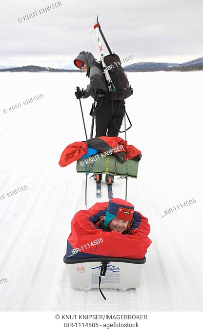 Sleigh ride in Lapland, girl, 4, being pulled in a pulka toboggan by her skiing mother over the frozen Holmajaervi Lake in Kiruna, Lapland, North Sweden, Sweden