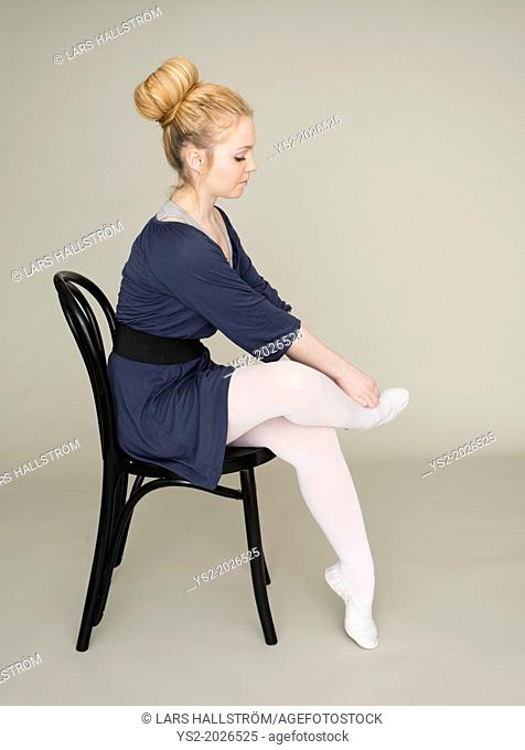 Young blond female teenager in ballet dress sitting on chair massaging foot