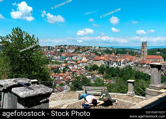 Fribourg, FR / Switzerland - 30 May 2019: view of the historic city of Fribourg with tourists relaxing near the Chapelle de la Lorette chapel