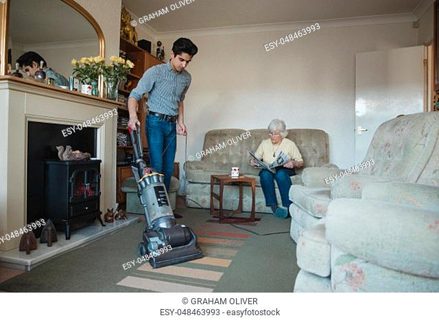 Teenage boy is hoovering his grandmother's living room for her while she reads a newspaper