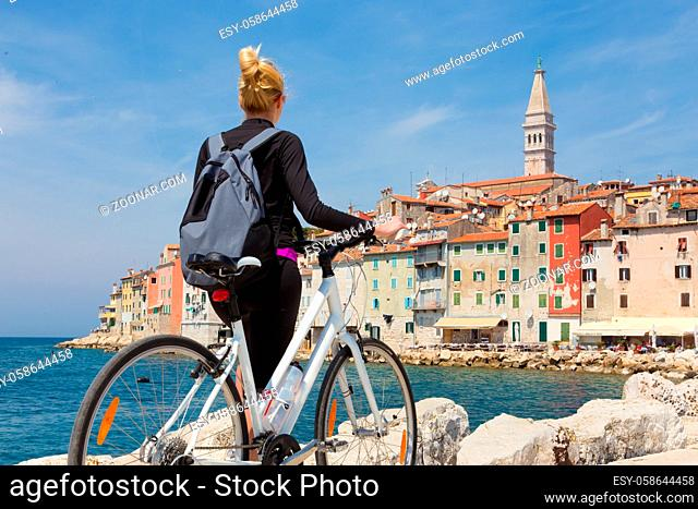 Young active female tourist cycling and enjoiying beautiful view of Rovinj, Istria, Croatia