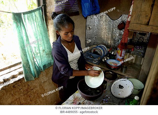Young woman washes dishes, household, Fianarantsoa province, Madagascar