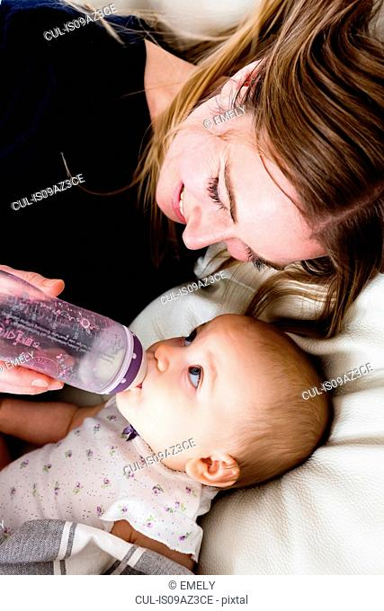 Overhead view of mid adult woman feeding bottle to baby daughter on sofa