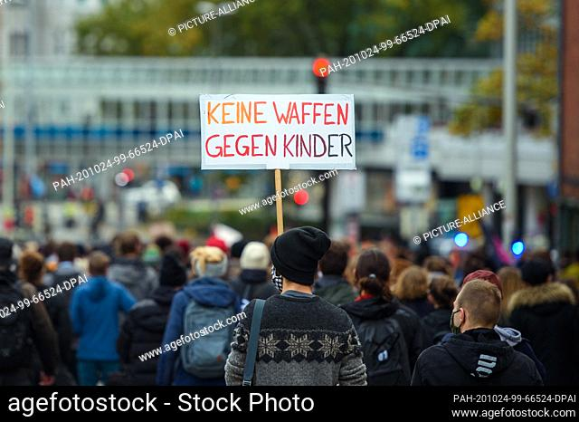 "24 October 2020, Schleswig-Holstein, Kiel: A participant walks through the city centre with a flag, """"No weapons against children"""""