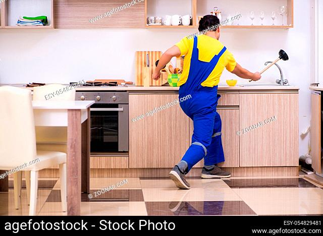 The young male contractor repairing tap at home