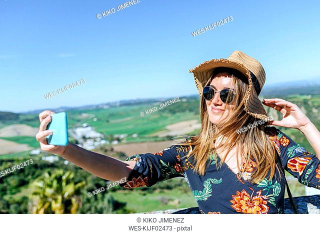 Spain, Cadiz, Vejer de la Frontera, portrait of smiling woman taking selfie with smartphone