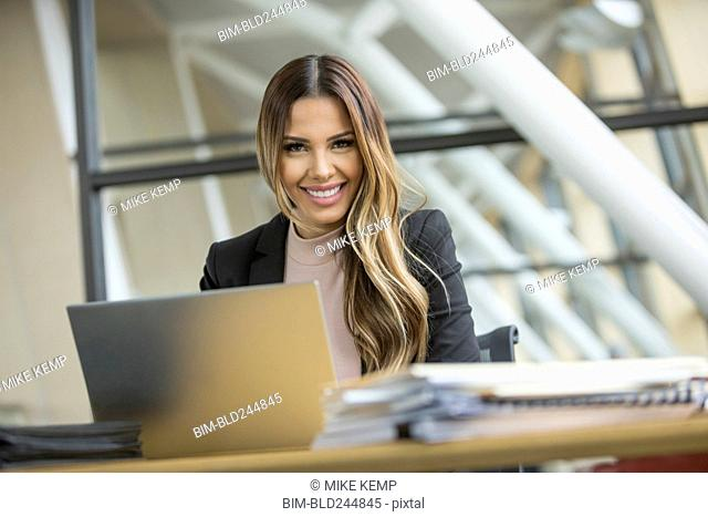 Smiling Mixed Race businesswoman using laptop