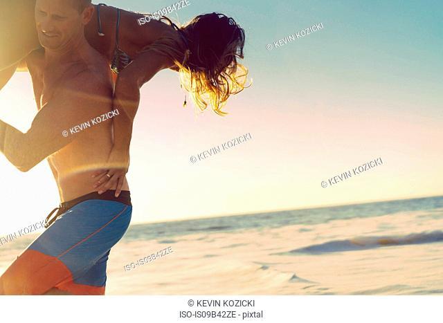 Man carrying girlfriend over shoulders at Newport Beach, California, USA