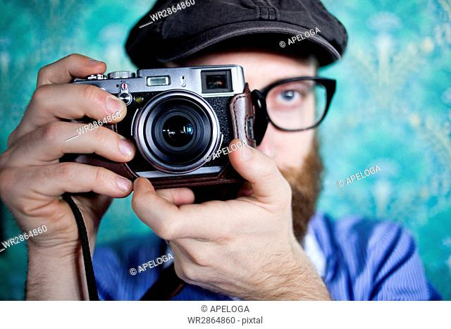 Close-up of man photographing through camera against wall