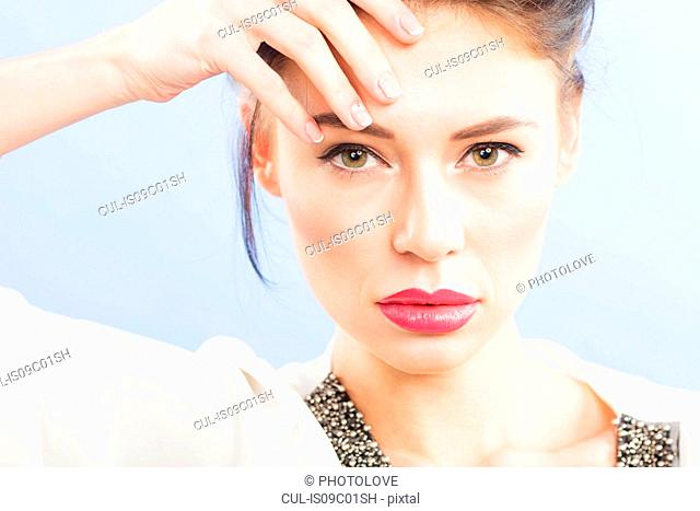 Beautiful young woman with hand on forehead, close up studio portrait