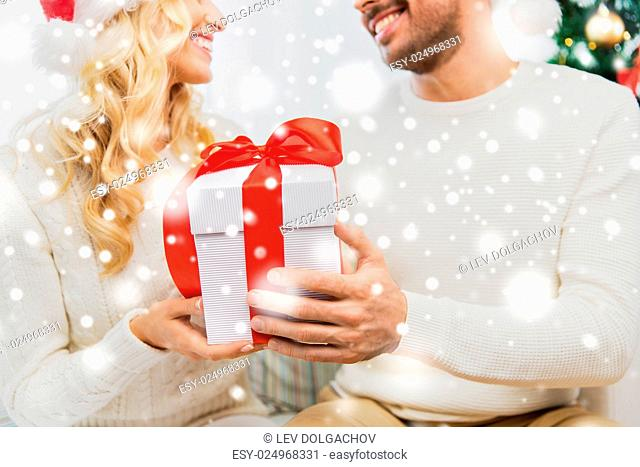 winter, holidays, christmas and people concept - close up of happy couple with christmas gift at home