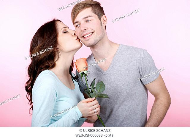 Young couple with rose, woman kissing to man