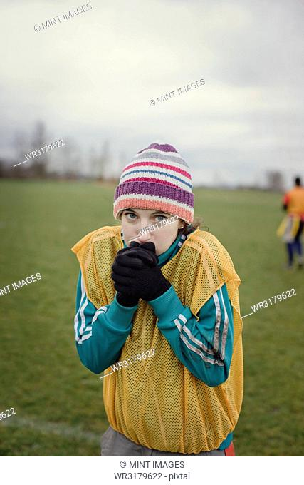 Caucasian woman blowing on her hands to stay warm at a sporting event in the winter