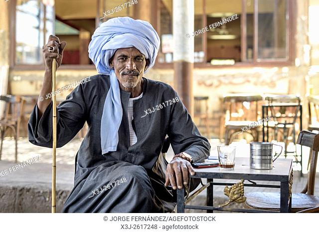 Portrait of a man with turban and typical ring drinking tea at a small bar terrace