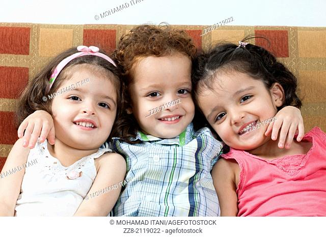 3 years olf triplets sat on sofa
