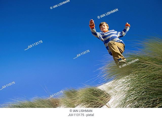 Exuberant boy jumping over sand dune beach grass