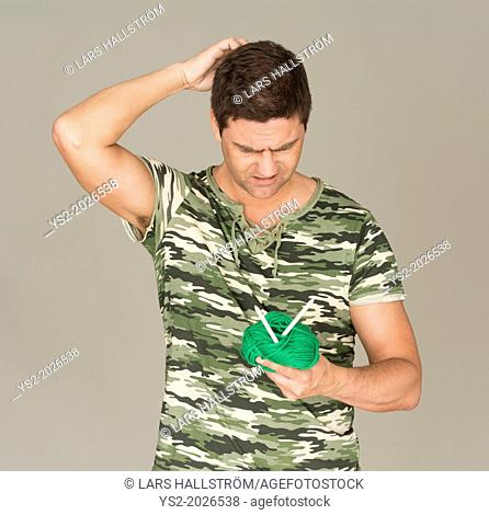 Man with camouflage t-shirt looking puzzled at a ball of yarn and knitting needles
