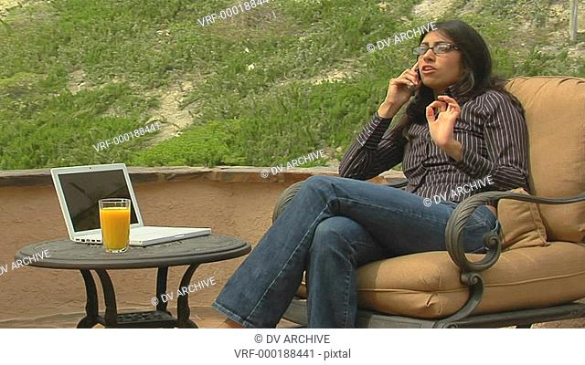 A woman speaks into a cell phone while sitting on a patio