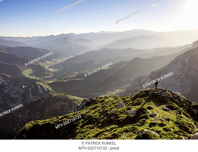 Man enjoying majestic view over mountains during hiking tour in Picos de Europa near the village of Potes, Cantabria, Spain