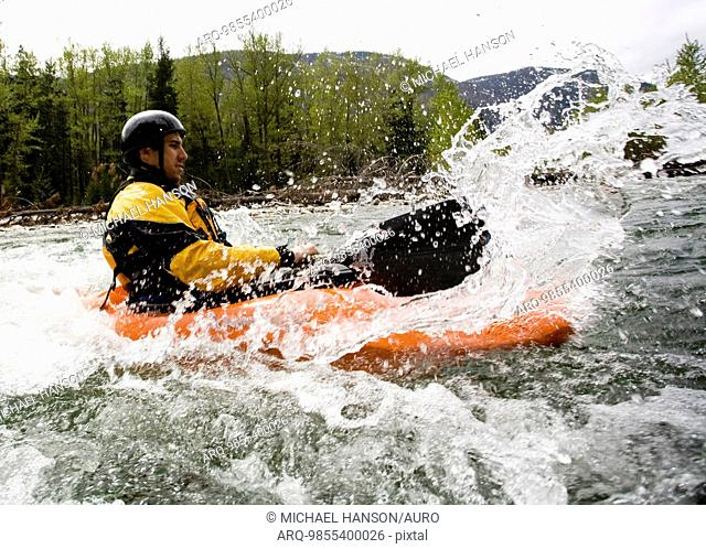 A playboater enjoys a small wave on a river