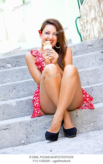 Young woman with a sandwich in her hands laughing