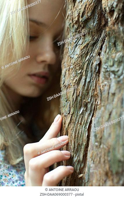 Young woman touching tree trunk
