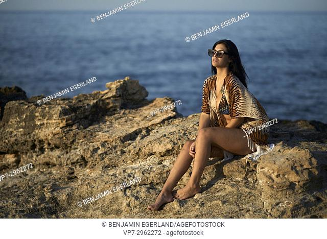 relaxed young woman enjoying last sunbeams of evening sun at Mediterranean beach. Greek ethnicity. 20 years old. In holiday destination Hersonissos, Crete