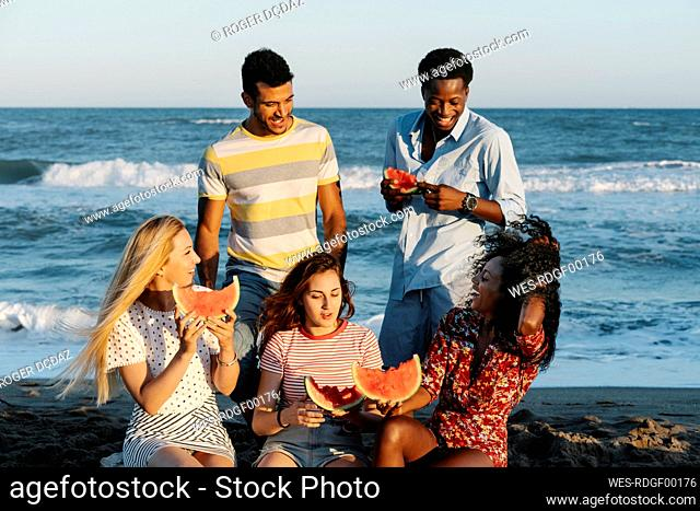 Friends enjoying while eating watermelon on sunny day