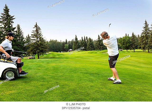 A male golfer drives a golf ball down the green with a wedge on a golf course while a disabled golfer in a specialized wheelchair watches; Edmonton, Alberta