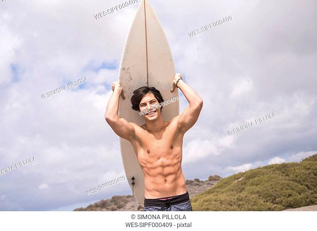 Portrait of smiling young man holding surfboard
