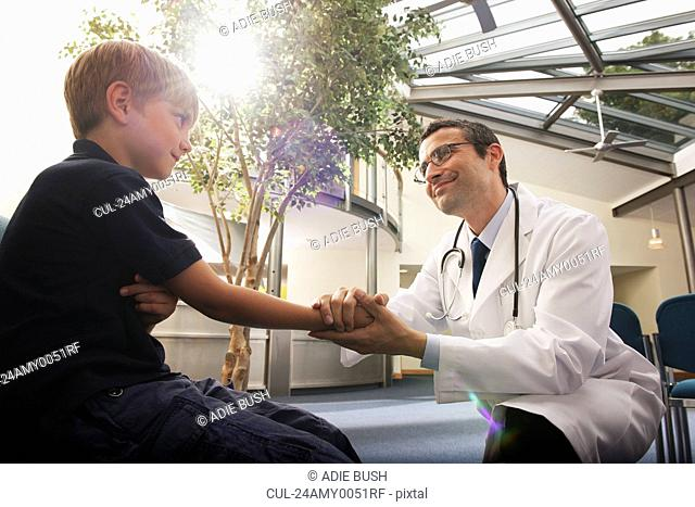 Doctor greeting young boy in surgery