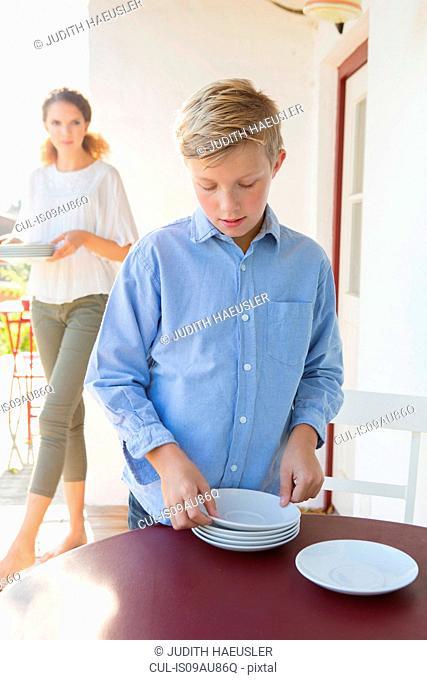 Boy preparing plates on patio table