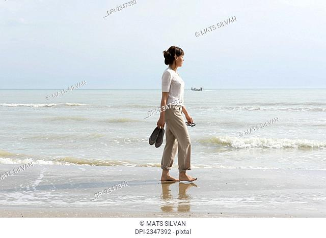 A woman walking on the wet beach carrying her shoes; Rimini, Emilia-Romagna, Italy