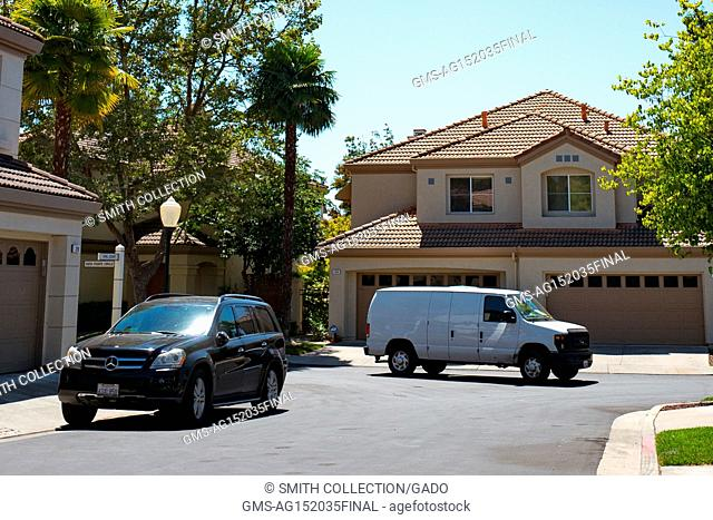 A white van for a third party Amazon.com delivery contractor drives down a suburban street in the San Francisco Bay Area town of San Ramon, California, July 26