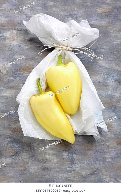 Still life with two yellow peppers and white paper over painted textile background. Overhead view