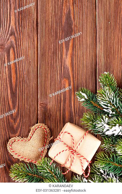 Christmas tree branch with snow, gift box and heart toy on wooden table. View with copy space