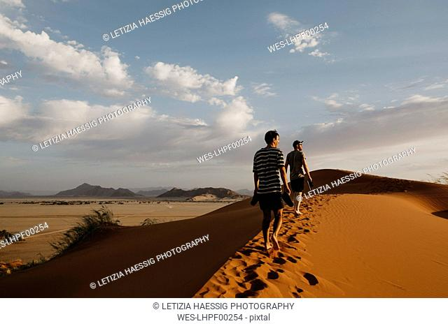 Namibia, Namib desert, Namib-Naukluft National Park, Sossusvlei, two men walking on Elim Dune at sunset