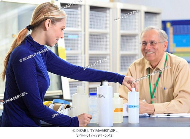 Engineering professor discussing chemical reagents with student in chemical laboratory