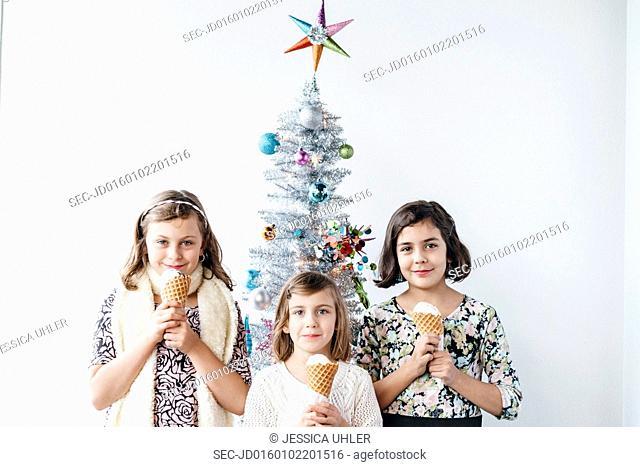 Girls with ice cream next to christmas tree