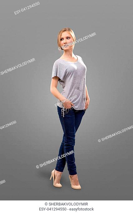 Woman in white t-shirt and jeans isolated on grey background