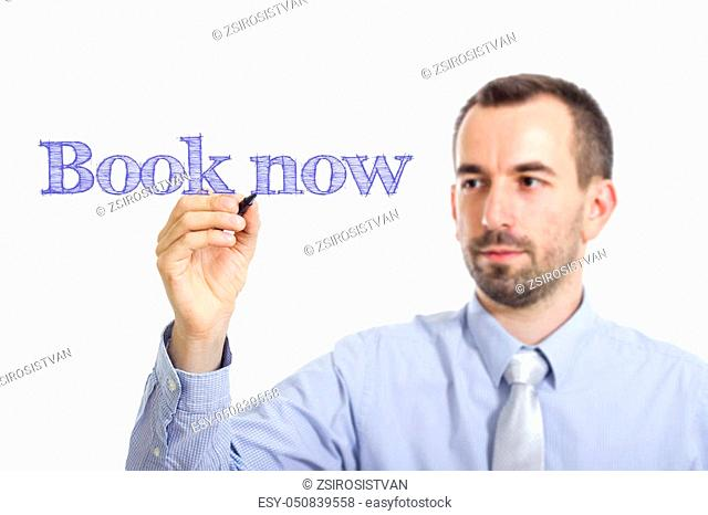 Book now - Young businessman writing blue text on transparent surface - horizontal image