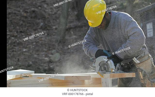 Carpenter using a circular saw to cut a rafter for a new home