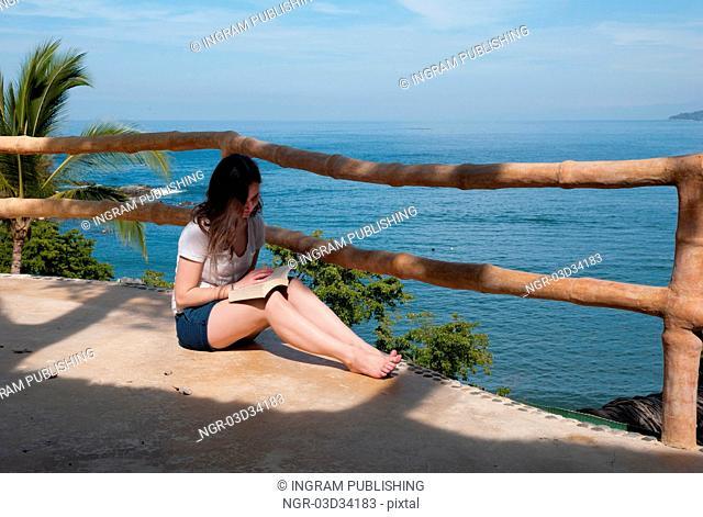 Teenage girl reading a book at the seaside, Sayulita, Nayarit, Mexico