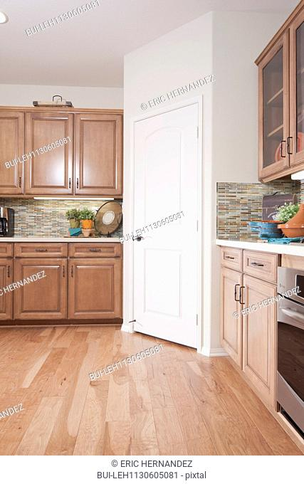 Wooden cabinets and closed door in kitchen