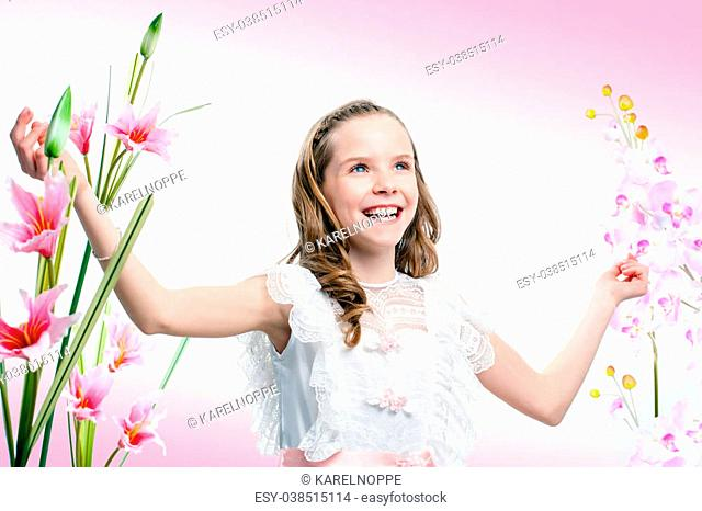 Close up portrait of happy young communion girl among flowers