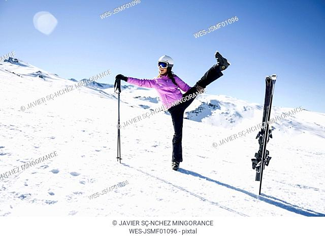 Woman wearing ski clothing stretching before skiing at the Sierra Nevada, Andalusia, Spain
