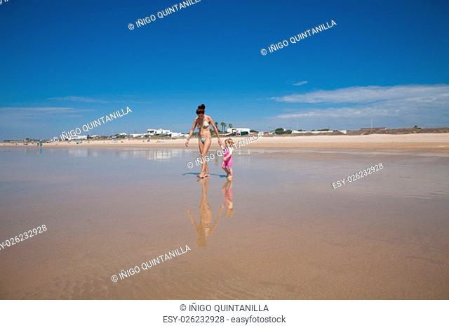 summer family of two years old blonde baby with pink and yellow swimsuit holding hand with brunette woman mother in bikini walking at sea shore beach sand in...